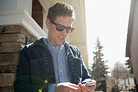 Attractive man texting on cell phone outside