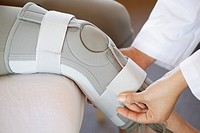 Doctor fastening knee brace on patient