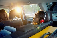 Young woman with headphones in the backseat of the car