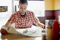 Man reviewing map at restaurant (thumbnail)