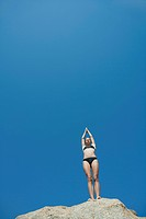 Girl in bikini standing against blue sky preparing to dive