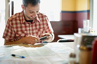 Man using cell phone and map to plan trip