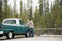 Father and son reviewing plans by old truck