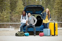 Friends posing with luggage and car