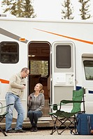 Couple relaxing with wine by camper