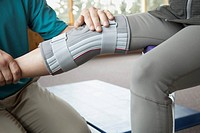 Therapist adjusting knee brace on patient