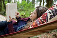 Pretty, mid-adult woman reading in hammock (thumbnail)