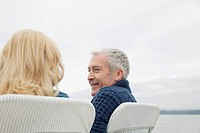 Middle_aged couple relaxing at lakeshore