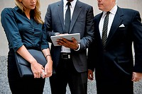 Three businesspeople looking at a digital tablet