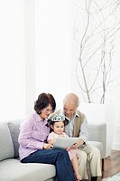 Grandparents with granddaughter 2_3 looking at digital tablet