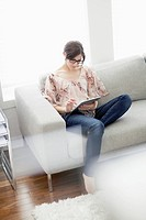 Woman sitting on sofa and using digital tablet