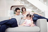 Parents with daughter 2_3 sitting on sofa and using digital tablet