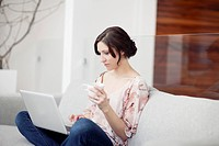 Young woman sitting on sofa with laptop