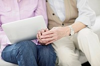 Mature couple using digital tablet, midsection