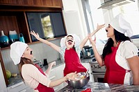 Mother with two daughters 10_12, 6_7 having fun while cooking