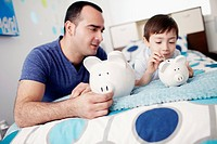 Father with son 4_5 holding piggybanks in bedroom