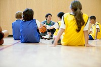 Basketball teams listening to teacher