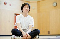 Asian, middle school student sitting on gym floor