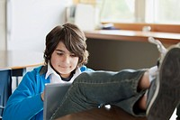 Male student with pc tablet and feet up on desk