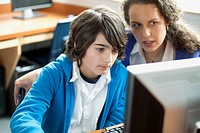 Teacher assisting middle school student on computer