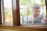 Middle aged man painting exterior window trim