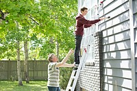 Father and son painting exterior of home.