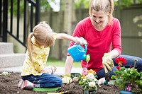 Mom and 5 year old daughter working on flower garden.