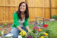 Pretty, latino woman planting flowers