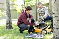Father and son maintaining lawnmower