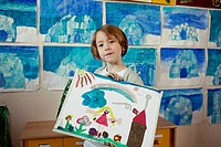 Happy school girl 6-7 showing her painting (thumbnail)