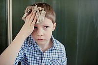 Schoolboy 8-9 wiping his forehead with paper towel (thumbnail)