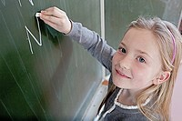 Happy young school girl 8_9 writing on blackboard
