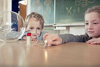 Schoolgirl 6_7 and boy 6_7 experimenting with electricity in science class