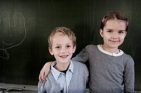 School boy 6-7 and girl 6-7 posing in front of blackboard (thumbnail)