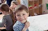 Young school boy 8_9 showing his drawing