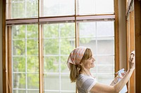 Middle aged woman washing windows in home