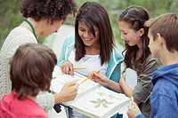 Students and teacher identifying plants.