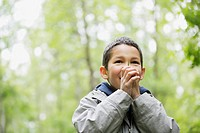 Elementary student using leaf to whistle
