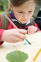 Elementary student painting leaf drawing outdoors.