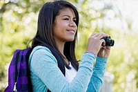 Female student with binoculars on field trip