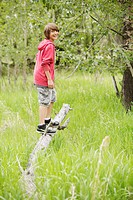 Middle school student standing on fallen tree branch.