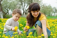 Boy with his mother collect spring flowers