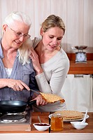 A mature mother and her adult daughter making crepes.