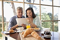 Couple using tablet pc at breakfast table