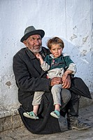 Old local man holding his granddaughter, Murgab, Tajikistan