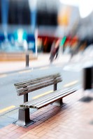 A lens blurred photo of an urban bench