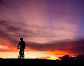 The silhouette of mountain bicycle rider on the hill with beautiful sunrise back