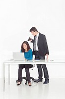 boy in office clothes ponting a gun to a girl