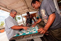 Bahamian men play checkers at a roadside food stall at Potter´s Cay in Nassau, Bahamas