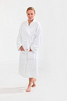 Woman in bath robe with hands in pockets